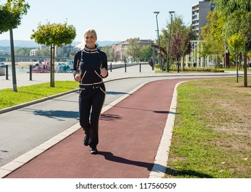 young girl jogging outdoor along trees path