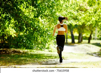 A young girl jogging in the park