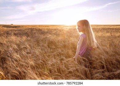 young girl joys at the wheat field at the evening time