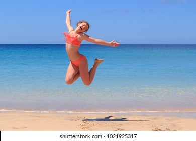 Young girl jumping in bikini at the beach on Canary Islands, Fuerteventura- Morro Jable