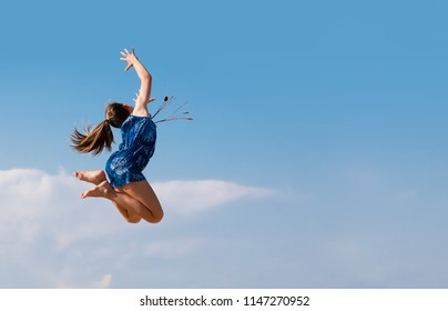 YOUNG GIRL JUMPING HIGH AS FLYING TURNING ROUND AGAINST THE BLUE SKY