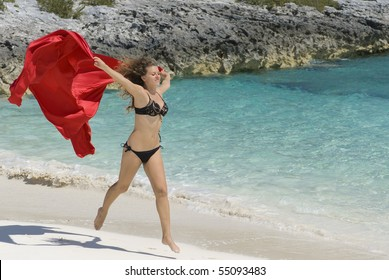Young girl jumping on the beach in the Caribbean