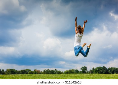 Young girl jumping on the meadow at the day time