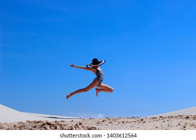 Young girl jumping over blue sky background. People, travel, fashion concept.