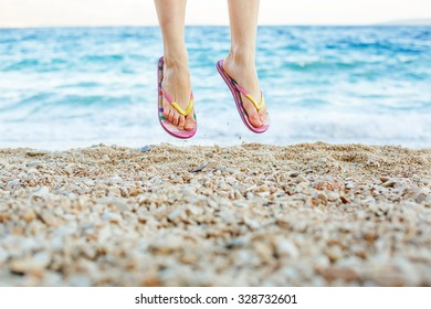 Young girl jumping in slippers on the beach. Summer fun