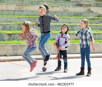 Young girl jumping while jump rope game with friends outdoor