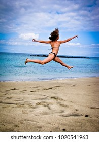 Young girl  jumps  high on the  ocean shore