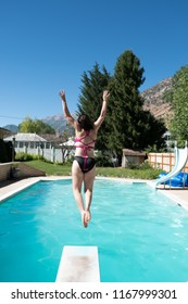 Young girl jumps off diving board into a backyard swimming pool. Woman entering the water after jumping off diving board. Girl in bikini mid air jumping into backyard swimming pool.