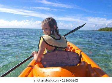 young girl kayaking on turquoise waters of the caribbean