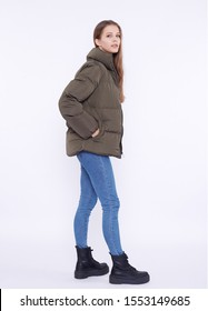 Young girl in a khaki down jacket isolated on a white background.