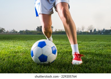 young girl kicking soccer ball on field