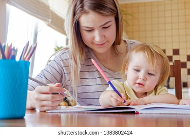Young girl kid drawing with her elder sister or mother using crayons, sitting at the table together. Low angle front portrait