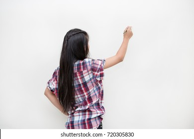 young girl kid drawing on white wall, Asian girl turn back to draw her creative artwork on white background