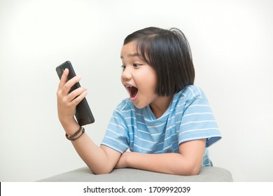 Young girl kid got shock and surprise when looking at smartphone device screen. Unsuitable content for children on internet or social media. Portrait of Asian kid on white background.