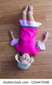 Young girl kid in pink dress and summer straw hat laying on the floor on her back and smiling, viewed full length from above, and looking at camera
