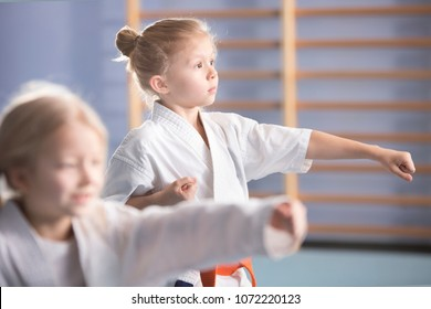 Young girl in kimono exercising during an extra-curricular karate class