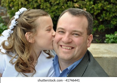 a young girl kisses her father on her first communion day