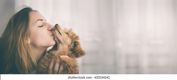 Young girl kissing her good friend dog . Background.