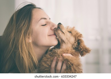 Young girl kissing her good friend dog .