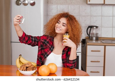 young girl in the kitchen with the phone, breakfast  and makes selfie
