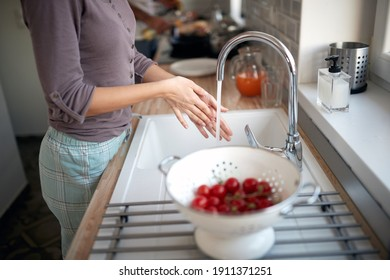 A young girl in the kitchen washing cherry tomatoes for a salad. Vegetables, kitchen, home, food