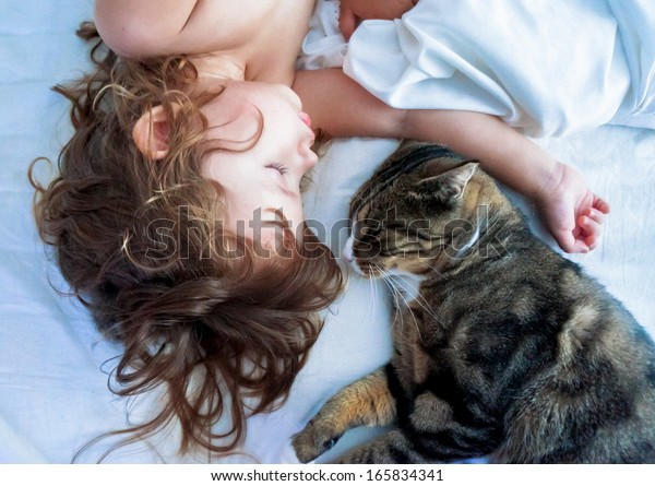Young girl and kitten sleeping on a white bed linen at home