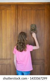 young girl knocking on front door of house using metal door knocker
