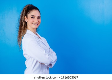 Young girl in lab coat on blue background with space for text. Woman with white coat. Concept of healthcare professional