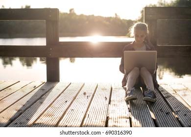 Young girl at the lake at sunset using laptop