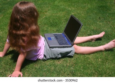 Young girl with laptop on grass