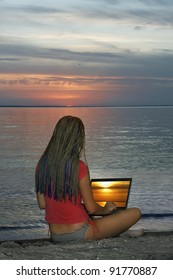 Young girl with laptop on sea shore on sunset background