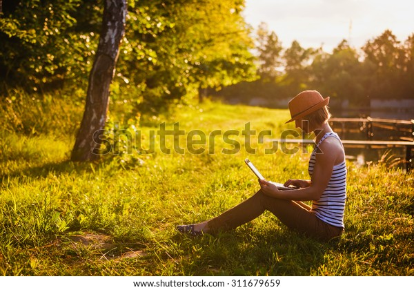 young girl with laptop outdoors