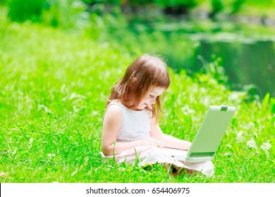 Young girl with laptop sitting on green grass in Park, Wroclaw, Poland