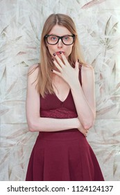 Young girl with large eyeglasses and hand on mouth