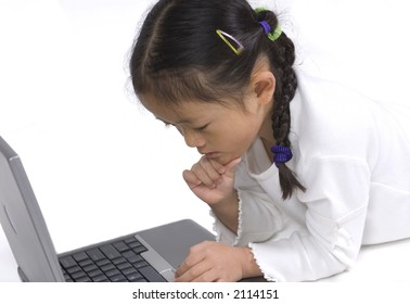 A young girl laying on the floor playing with a laptop