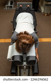 A young girl lays on her stomach on a Chiropractic adjustment table waiting for the Chiropractor to come work on her.