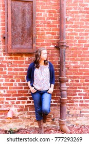 Young Girl Leaning Against Old Red Brick Wall
