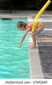 Young girl leaning over swimming pool with wet hair