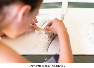 Young girl learning on the course of architectural design for children - preparing architectural model