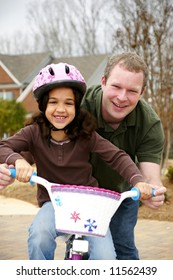Young girl learning to ride a bike