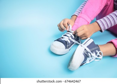 Young girl learning to tie her shoes, Copy space for word