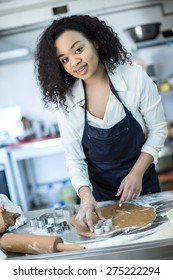A young girl learns to cook cakes in the bakery