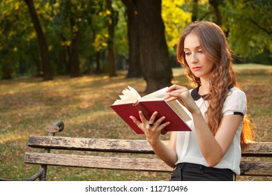 A young girl learns in the park