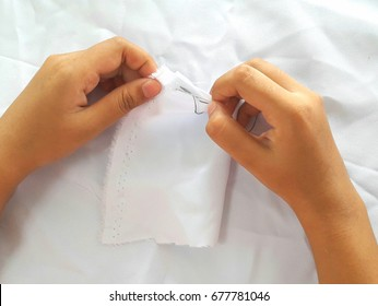 young girl learns sewing with a needle
