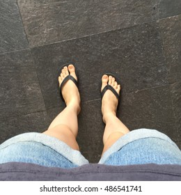 Young Girl Legs in Black Flipflop Sandals on Floor or Grunge Great For Any Use.