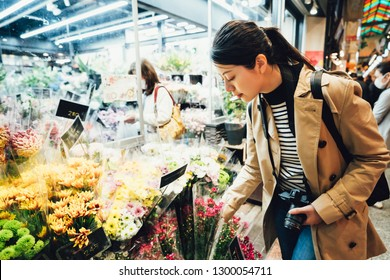 young girl lens man touching picking flower in plants vendor in nishiki ichiba. beautiful traveler holding camera buying flora in brocade market. asian woman shopping in local japanese place kyoto.
