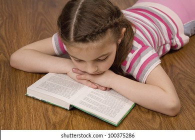 young girl lies on wooden floor on the abdomen and attentively reading book