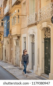a young girl in lifestyle clothes strolling through the narrow streets of an ancient city with old doors and balconies