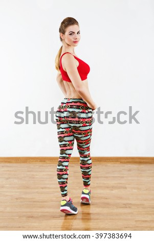 201f9b62743bc Young girl with light brown hair wearing colorful leggings and red short  top standing at gym
