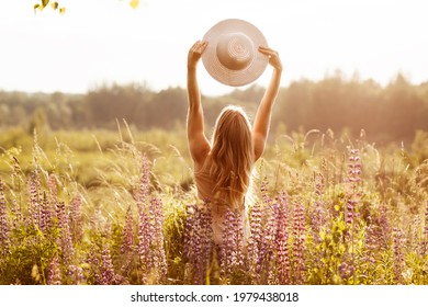 A young girl in a light dress with a hat on her outstretched arms on a lupine field, looking at the sunset. Rear view, space for text